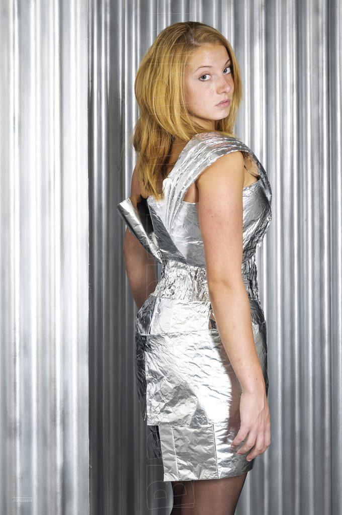 Model in cocktailjurk van aluminiumfolie.