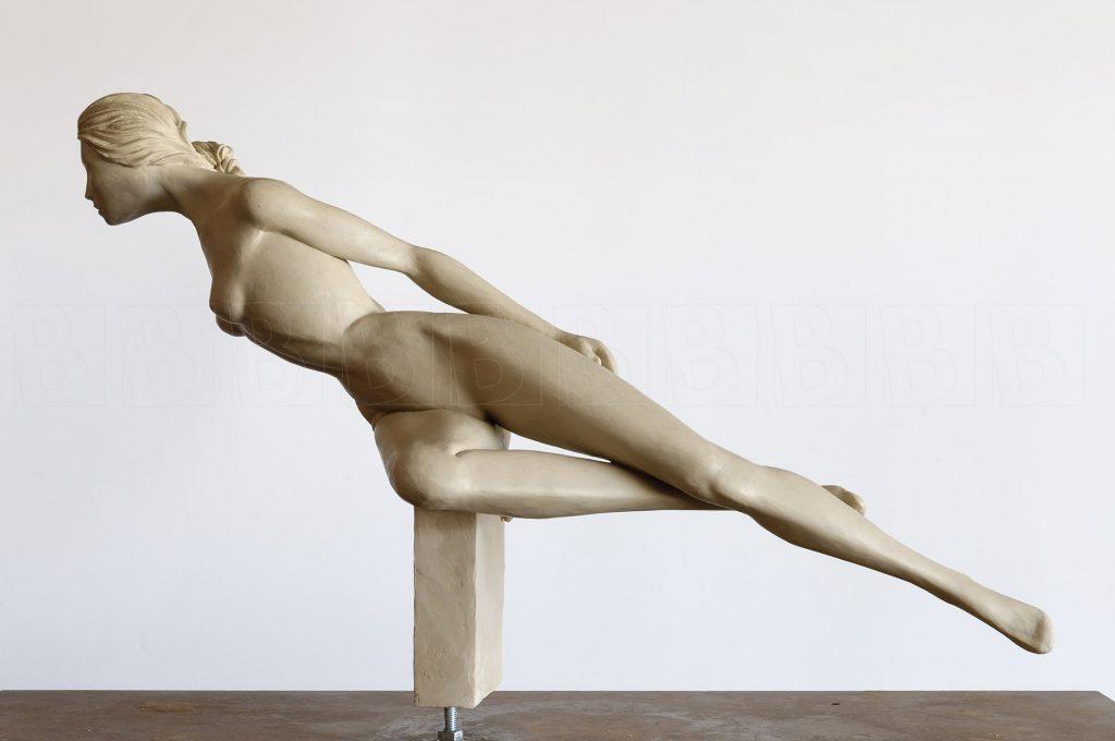Vrouw strekt zich uit, zittend op een blok.