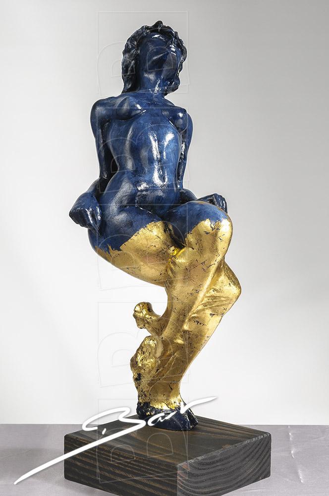 Betaalbare sculptuur van vrouw op een hertenhoef in blauw en goudkleurig bladmetaal.
